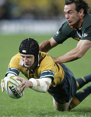 Australia's Stephen Larkham stretches to score a try - AP Photo/Rob Griffith