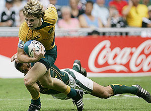 Australia's James O'Connor, left is tackled at the Hong Kong Rugby Sevens (AP Photo/Kin Cheung)