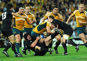 Australian Adam Ashleigh Cooper (centre) is tackled by New Zealand\'s Jimmy Cowan (right) and Ali Williams (left) during the Tri Nations final between the Australian Wallabies and New Zealand All Blacks at Suncorp Stadium in Brisbane, Saturday, Sept. 13, 2008. The All Blacks beat the Wallabies 28-24. AAP Image/Dave Hunt