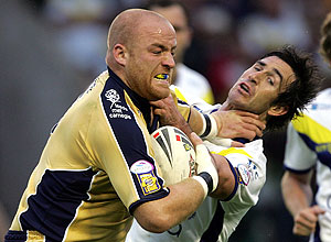 Australian Rugby League player Andrew Johns, right, is handed off by Leeds Rhinos' Danny Ward as Johns makes his debut for Warrington Wolves during their Super League game at the Halliwell Jones Stadium, Warrington, England. AP Photo/Paul Ellis