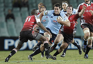 Waratahs' Dave Dennis, center, tries to sidestep Lions' Wandile Mjekevu. AP Photo/Rob Griffith