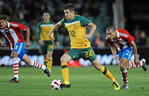 Australia's Dario Vidosic (centre) takes the ball up field despite pressure from Paraguay's Dario Veron. AAP Image/Dean Lewins