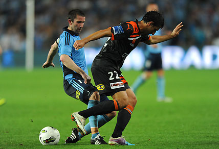 Sydney FC's Terry McFlynn tackles the Brisbane Roar's Thomas Broich.