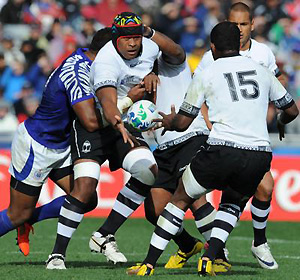 Fiji's Akapusi Qera passes the ball to Fiji's full back Kini Murimurivalu