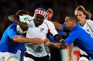 US right wing Takudzwa Ngwenya (centre) is tackled by Italy's scrum half Fabio Semenzato. AAP Image/AFP/Martin Bureau