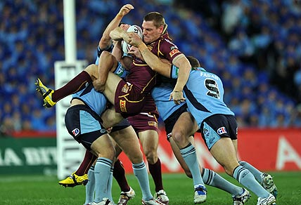 Queensland's Brent Tate (centre) is tackled by Greg Bird (left), Mitchell Pearce and Robbie Farrah (right) of New South Wales during game 2 of the State of Origin Rugby League series in Sydney on Wednesday, June 13, 2012. (AAP Image/Paul Miller