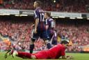 Liverpool's Luis Suarez, bottom, smiles after appearing to dive. AP Photo/Jon Super