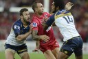 Queensland Reds player Quade Cooper (centre) is help by ACT Brumbies' Henry Speight (right) and Nic White during their round 10 Super Rugby match at Suncorp Stadium in Brisbane, Saturday, April 20, 2013. (AAP Image/Dan Peled)