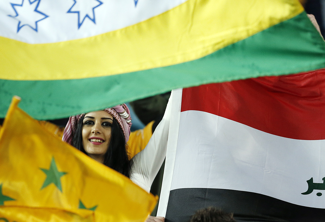 An Iraqui fan peers through flags before the start of the match at Stadium Australia. (Photo: Paul Barkley/LookPro)
