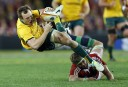 Jesse Mogg of the Wallabies is sent flying after a tackle by Geoff Parling of the Wallabies. (Photo: Paul Barkley/LookPro)