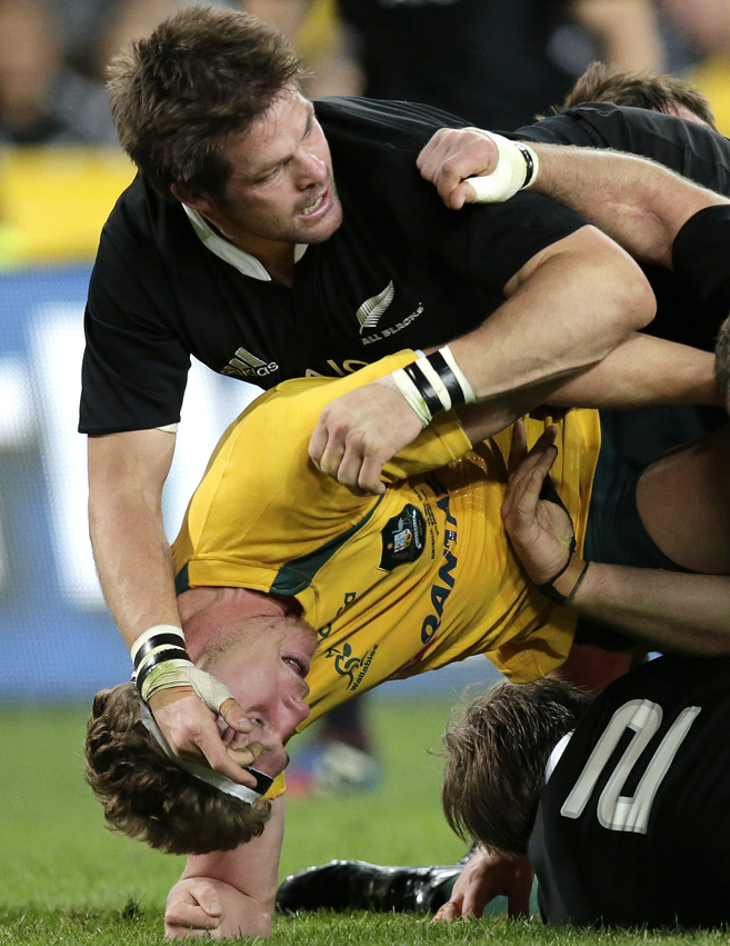 New Zealand's Richie McCaw, top, gets the upper hand on his Australian open side counterpart Michael Hooper