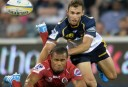 Brumbies' Nic White (right) tackles Reds' Will Genia