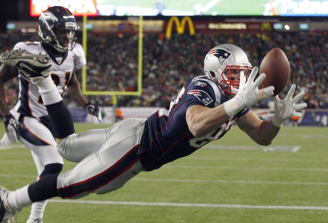 New England Patriots tight end Rob Gronkowski (87) catches a 10-yard touchdown pass while being defended by Denver Broncos cornerback Andre' Goodman (21) during the first half of an NFL divisional playoff football game Saturday, Jan. 14, 2012, in Foxborough, Mass. (AP Photo/Charles Krupa)