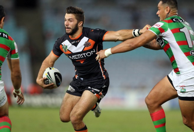 James Tedesco of the Wests Tigers fends off souths rabbitohs player