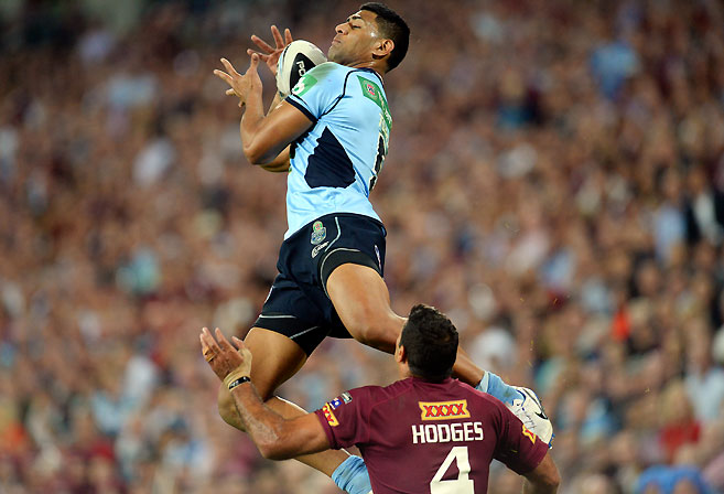 NSW Blues player Daniel Tupou leaps for a ball ahead of Queensland's Justin Hodges during Game one