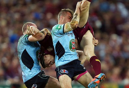 New South Wales' Beau Scott and Josh Reynolds lift Brent Tate in a tackle during Game 1 of the 2014 State of Origin series. Reynolds was placed on report for the tackle. (Image: AAP)