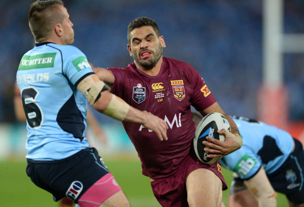 Greg Inglis puts a big fend on Josh Reynolds (Photo: AAP)