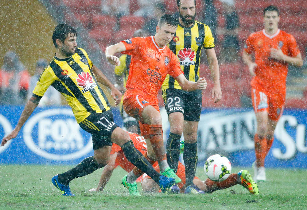 Roar midfielder Matt McKay (centre) in the rain