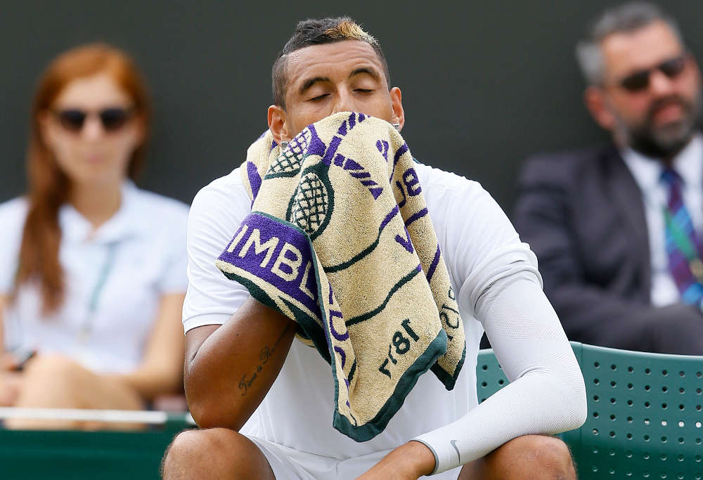 Nick Kyrgios of Australia wipes his face with a towel