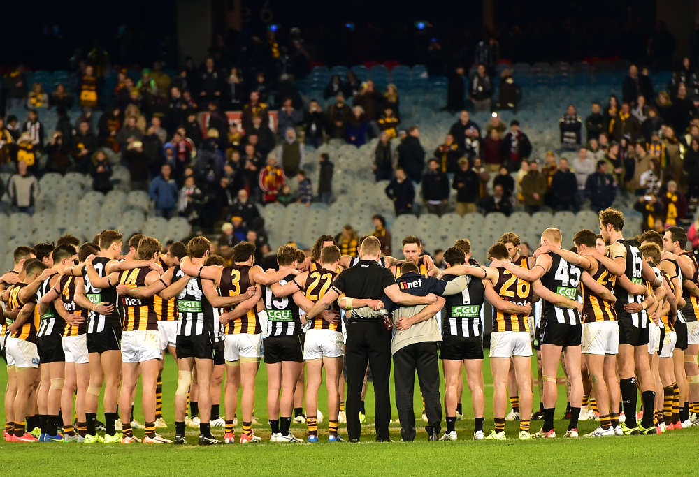 Collingwood and Hawthorn staff links arms in tribute of Phil Walsh.