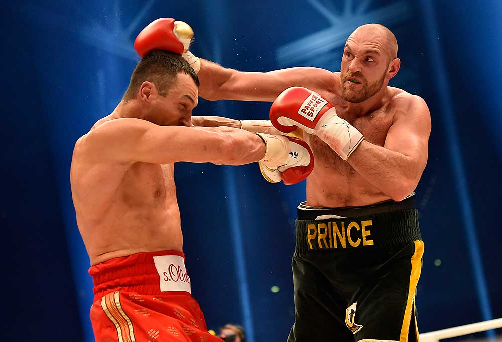Ukraine's Wladimir Klitschko, left, and Britain's Tyson Fury, right, exchange blows