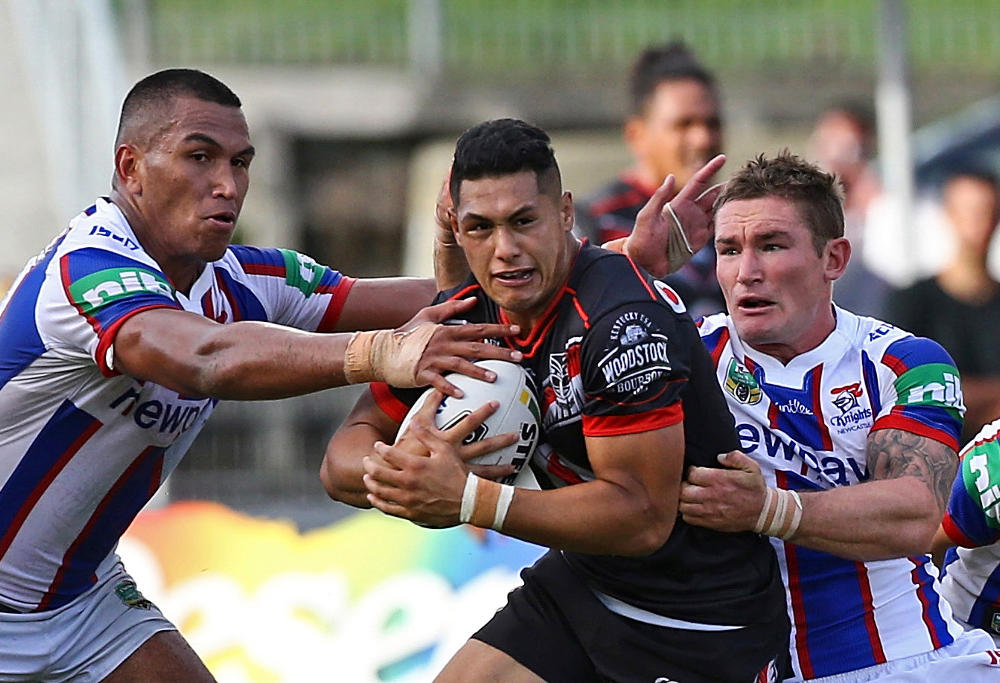 Jacob Saifiti, left, and Tyler Randell of the Newcastle Knights tackle Roger Tuivasa-Sheck of the Warriors