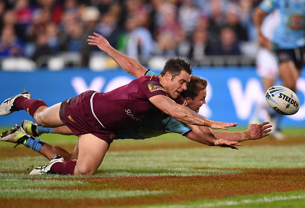 Matt Moylan of the Blues beats Cooper Cronk of the Maroons to the ball