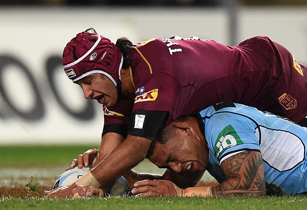 Tyson Frizell of the Blues is tackled by Johnathan Thurston of the Maroons