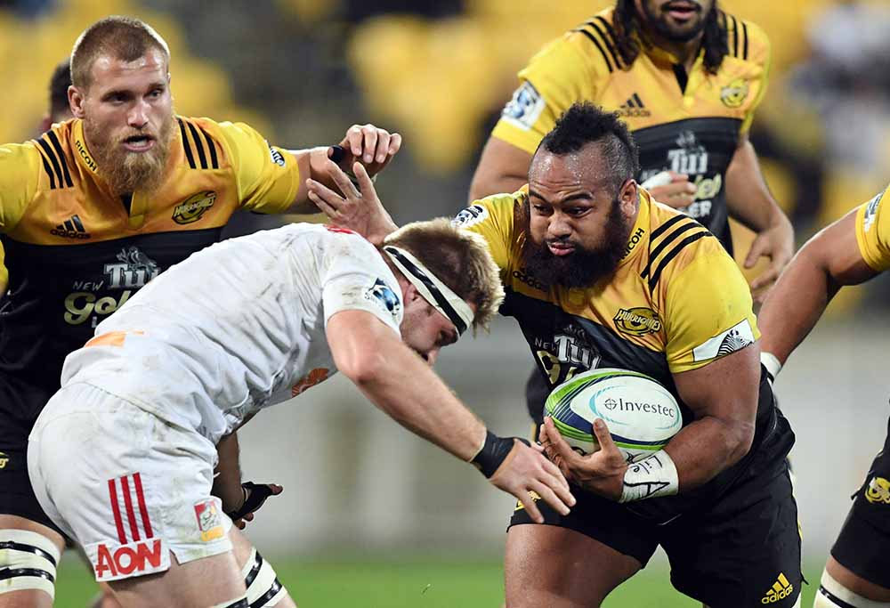 Loni Uhila of the Hurricanes, right, fends off Sam Cane of the Chiefs