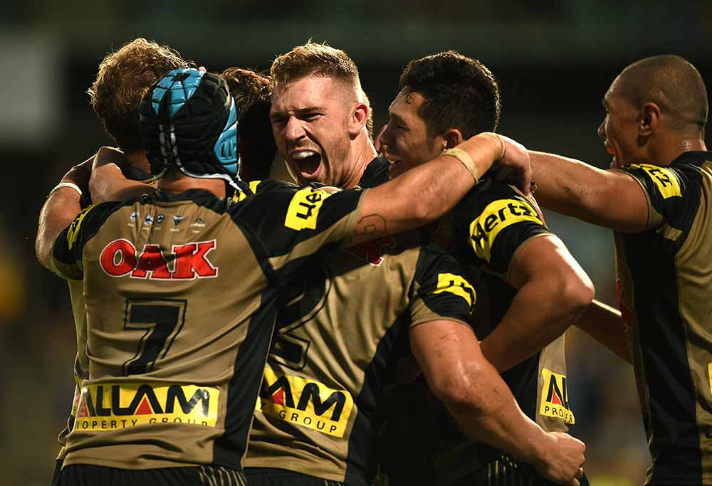 Bryce Cartwright of the Panthers, (centre), celebrates with team mates