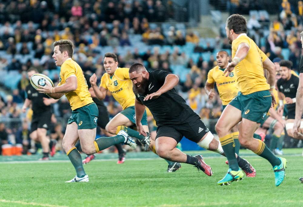Wallabies' flyhalf Bernard Foley is chased by All Blacks' prop Charlie Faumuina