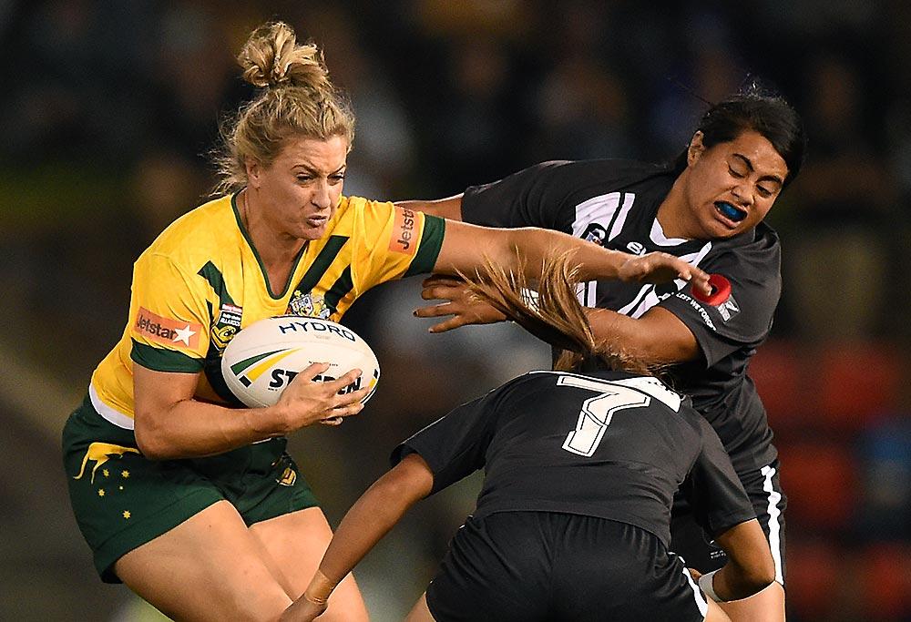 Ruan Sims of the Jillaroos (left) palms off a tackle by Maitua Feterika of the Kiwi Ferns