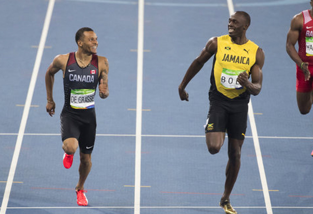 Usain Bolt and Andre de Grasse share a lighter moment as they cross the line during the 100m semi-final at the Rio Olympics