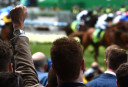 A racegoer punches his fist in the air